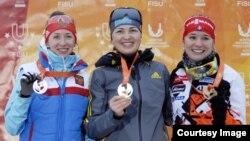 Қазақстандық биатлоншы Алина Раикова (ортада) қысқы универсиаданың алтынын алған сәті. Осрблье. 25 қаңтар 2015 жыл.