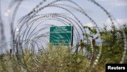 Предупреждающий знак и проволочная баррикада вдоль де-факто границы Грузии и Южной Осетии
