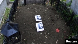 Two pictures of former communist dictator Nicolae Ceausescu lie on his grave after it was dug up to check whether it really contained his remains.