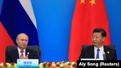 CHINA -- China's President Xi Jinping and Russia's President Vladimir Putin attend a signing ceremony during Shanghai Cooperation Organization (SCO) summit in Qingdao, Shandong Province, China June 10, 2018