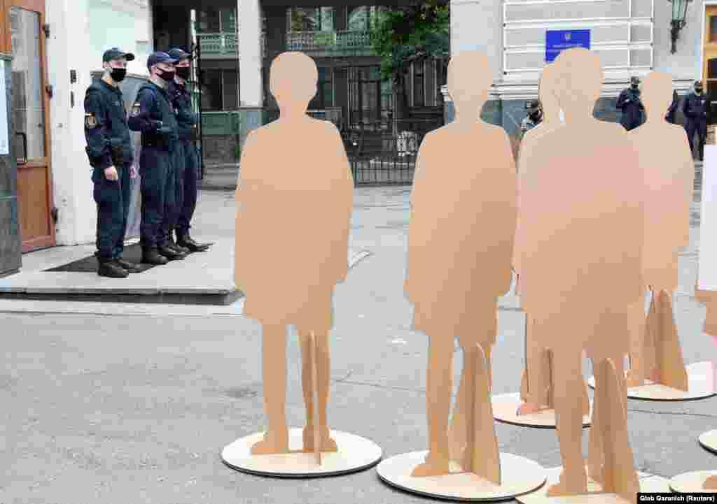 Поліцейські в масках на варті під час мітингу біля Міністерства охорони здоров'я в Києві. Мітингувальники дотримуються карантину. Людей здебільшого представляють манекени (REUTERS/Gleb Garanich)