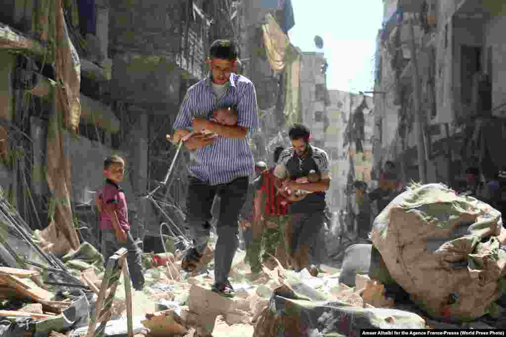Syrian men carrying babies make their way through the rubble of destroyed buildings following a reported airstrike on the rebel-held al-Salihin neighborhood of Aleppo on September 11, 2016.  Spot News -- First Prize, Stories (Ameer Alhalbi for AFP)