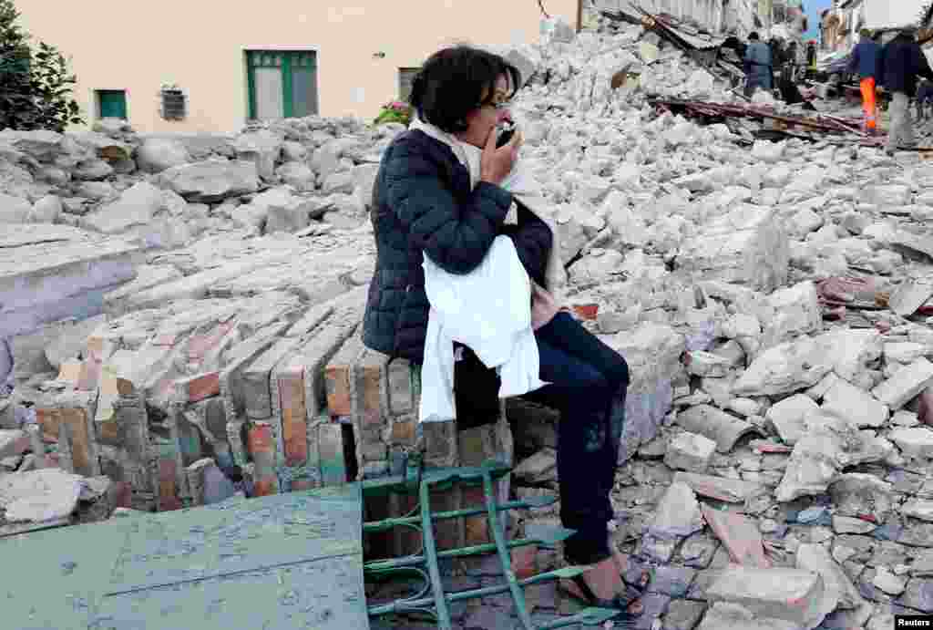 A woman sits amid rubble in Amatrice in central Italy following a strong earthquake. The 6.2-magnitude quake has killed at least 247 people. (Reuters/Remo Casilli)