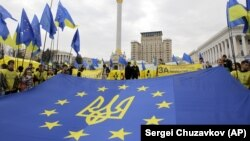"Ukraine – Activists of Ukrainian movement ""For European Future"" hold EU flag with the Ukraine national emblem during their rally at Independence Square in Kyiv on October 30, 2013"