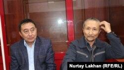 Обвиняемый в участии в деятельности ДВК Еркин Казиев (справа) в суде со своим адвокатом Галымом Нурпеисовым. Алматинская область, 15 октября 2019 года.