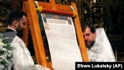 Священники ПЦУ представляют томос об автокефалии для Православной церкви Украины после Рождественской литургии в Софийском соборе в Киеве, 7 января 2019 года