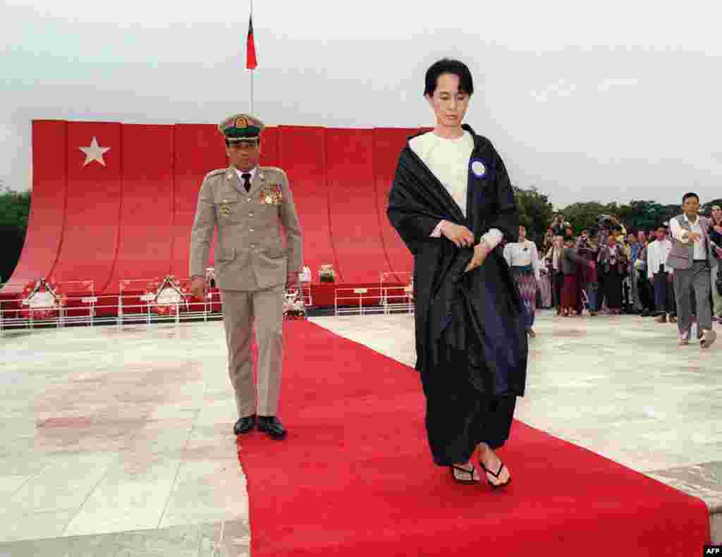 Aung San Suu Kyi, followed by Lieutenant Colonel Than Tun from the Myanmarese government, lays a bouquet of flowers at the tomb of her assassinated father, Burmese liberation hero Aung San, on Martyr's Day in Yangon in 1995.