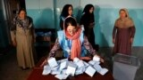 An Afghan election commission worker prepares ballot papers for counting in Kabul.