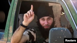 An Islamic State fighter gestures from a vehicle near the Syrian town of Kobani after IS fighters took control of the area in October 2014. When it comes to working face-to-face to deradicalize young people, there appears to be little difference between the methods used with neo-Nazis and with foreign fighters from IS or Al-Qaeda. (file photo)