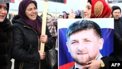 Chechen woman holds a picture of Ramzan Kadyrov during a rally in central Grozny earlier this year.