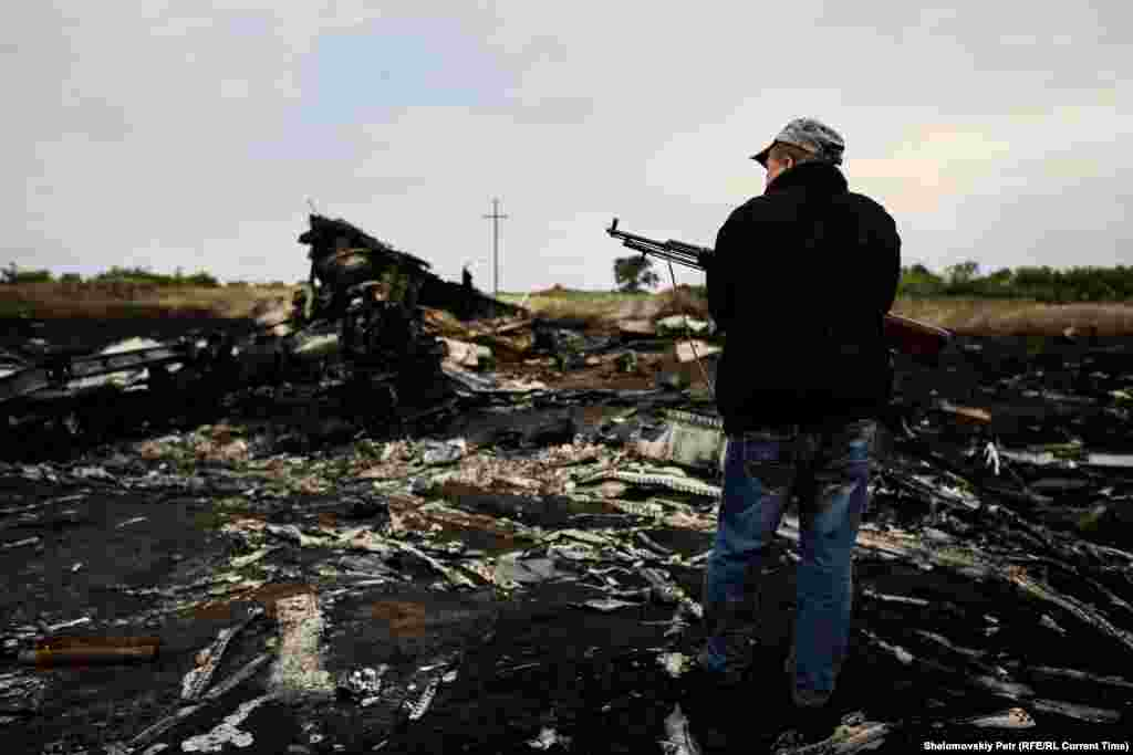 An armed separatist fighter surveys the crash site.