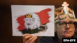 Вечерта след тайната церемония протестиращите носеха плакати, на които Лукашенко е изобразен като мишка с корона