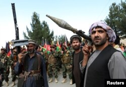 Armed men stand next to Afghan security forces in a show of solidarity against the Taliban, on the outskirts of Kabul on June 23.