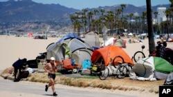 Egy futó halad el hajléktalanok tábora mellett 2021. június 8-án a kaliforniai Los Angeles Venice Beach városrészében