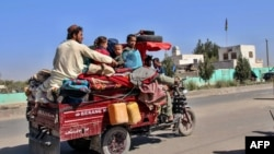 Internally displaced Afghans flee from Nadali district to Lashkar Gah in Helmand during clashes between Taliban fighters and Afghan security forces on October 14
