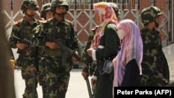 Мусульманки и китайские силовики, архивное фото