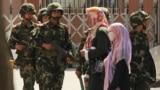 Группа уйгурских женщин-мусульманок на фоне патруля китайской армии. Урумчи, 2016 год