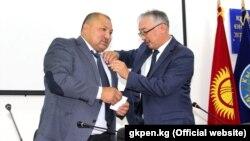Председатель ГКПЭН Уланбек Рыскулов наградил депутата парламента Кожобека Рыспаеванагрудным знаком «Каарман». 5 сентября 2018 года.