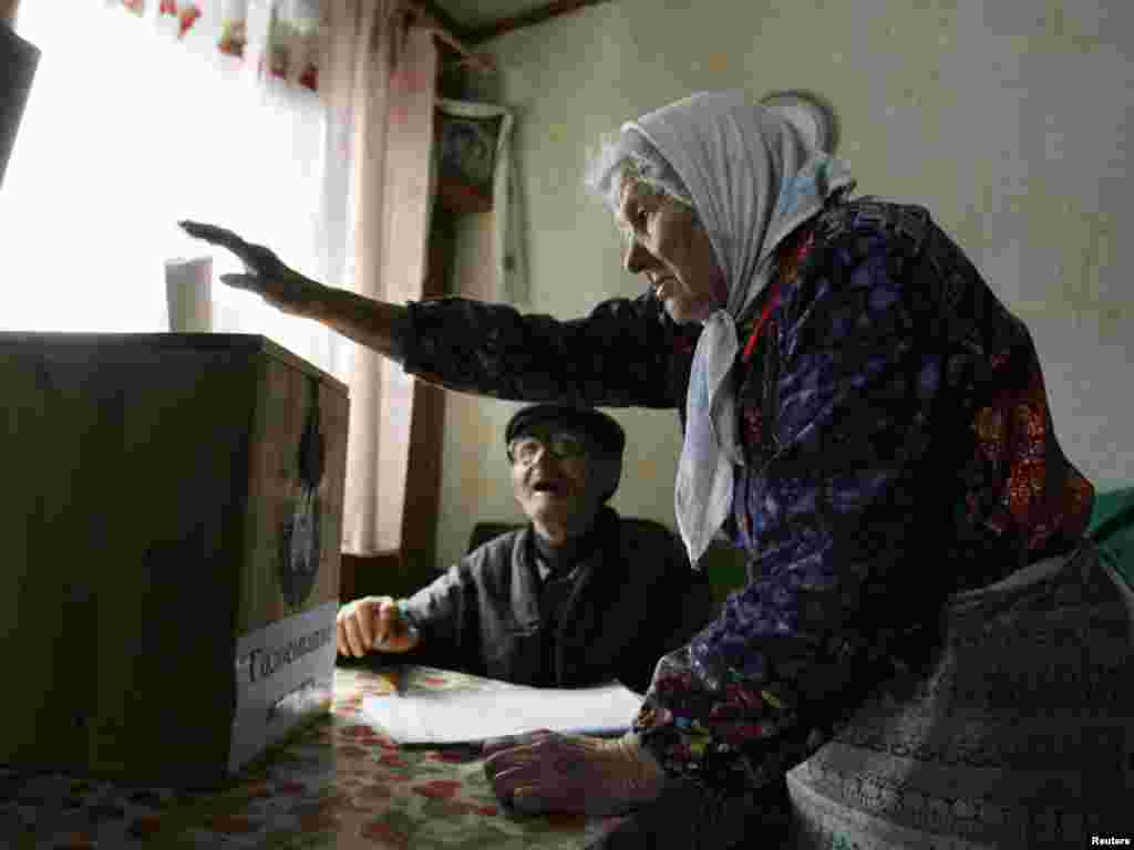 A woman casts a ballot from home in the village of Korolev Stan.