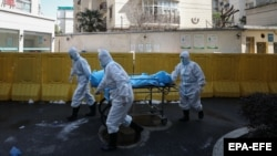 چین کې د کرونا ویروس له امله لیدل کېږي چې یو مړی لېږدول کېږي.