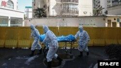 Сотрудники в защитных костюмах перевозят тело умершего в китайском городе Ухань во время вспышки коронавируса. 16 февраля 2020 года.