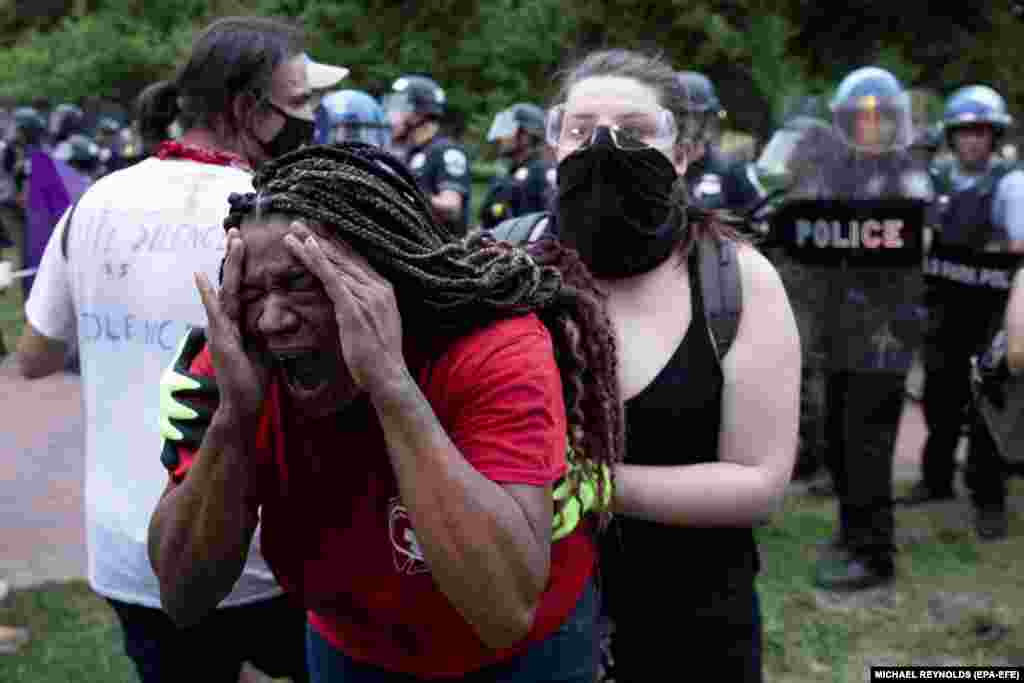 A woman (Left) reacts after being sprayed with chemical agents as police clear out Lafayette Park across the street from the White House after protesters attempted to pull down the Andrew Jackson statue in the park, in Washington DC, USA, 22 June2020. Police used chemical agents to clear out Lafayette Park and skirmishes broke out between protesters and police.