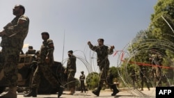 Members of the Afghan military use barbed wire to secure the road which leading to Kabul's military hospital after a bomb blast there killed six people.
