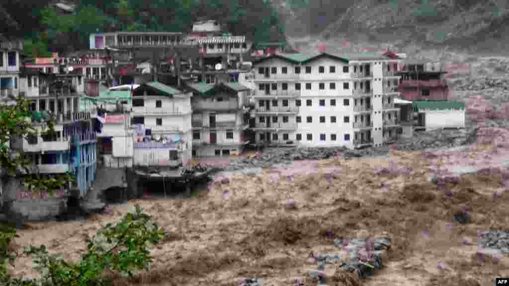 Fast-moving water from the Alaknanda River destroys building during a heavy monsoon in the Indian state of Uttrakhand. At least 18 people have been killed as the annual monsoon covered the country nearly two weeks ahead of schedule. (AFP)
