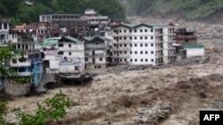 Indi – Monsunet shkaktojnë daljen e lumenjve nga shtrati, dhe si rrjedhojë ujërat e rrëmbyeshme nga lumi Alaknanda shkatërrojnë ndërtesat, 17Qershor2013
