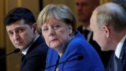 Ukraine's President Volodymyr Zelenskiy and German Chancellor Angela Merkel listen to Russia's President Vladimir Putin as they attend a joint news conference in Paris on December 10.