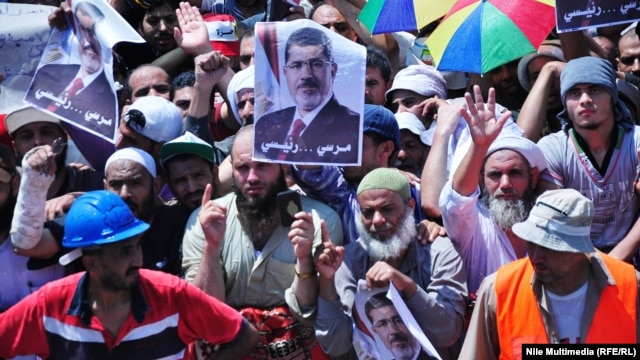 Supporters of the deposed Egyptian President Muhammad Morsi wave his portrait in a protest near the Rabia al-Adawiya Mosque in Cairo on August 1.