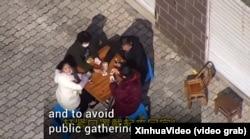 Поліцейський дрон заганяє до приміщення компанію, яка грає у карти на дворі. Китай, лютий 2020 року