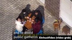 Полицейский дрон загоняет в помещение компанию, которая играет в карты на дворе. Китай, февраль 2020 года
