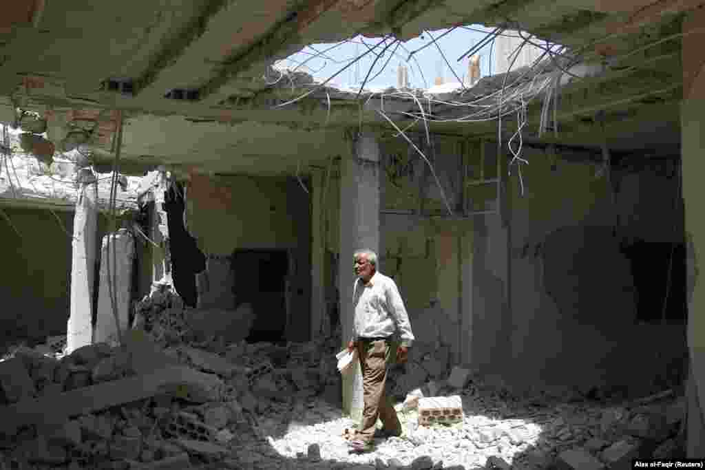 A man walks amid rubble at a damaged site in the province of Daraa, Syria. (Reuters/Alaa al-Faqir)