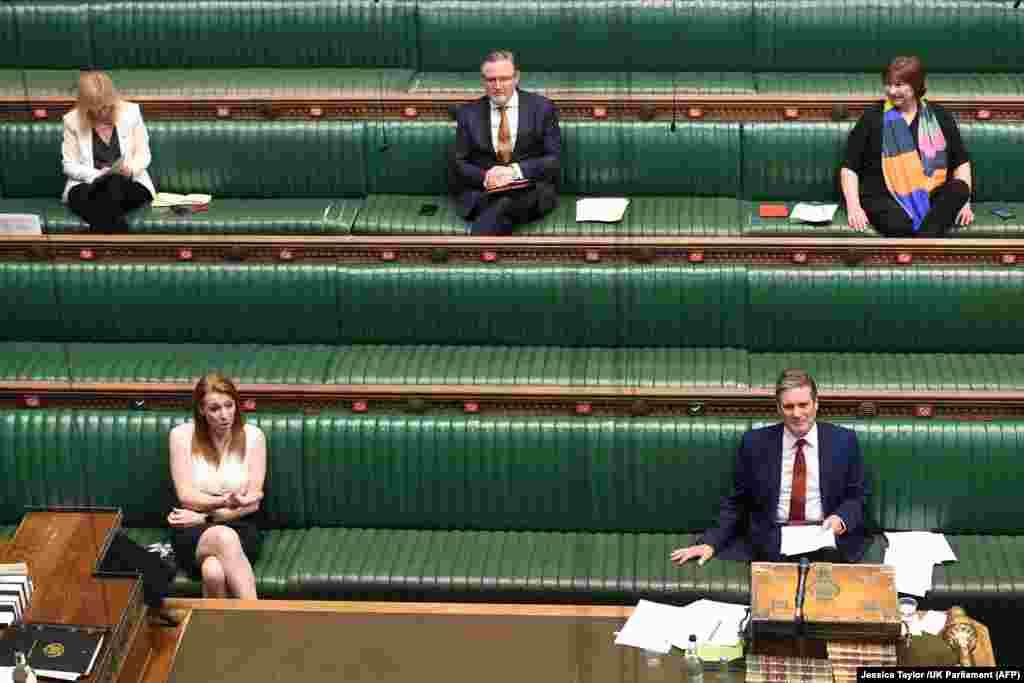 На фотографії, оприлюдненій парламентом Великої Британії, лідер опозиційної Лейбористської партії Кір Стармер (праворуч унизу) й інші депутати Палати громад дотримуються відстані на сесії запитань до прем'єр-міністра 20 квітня 2020 року