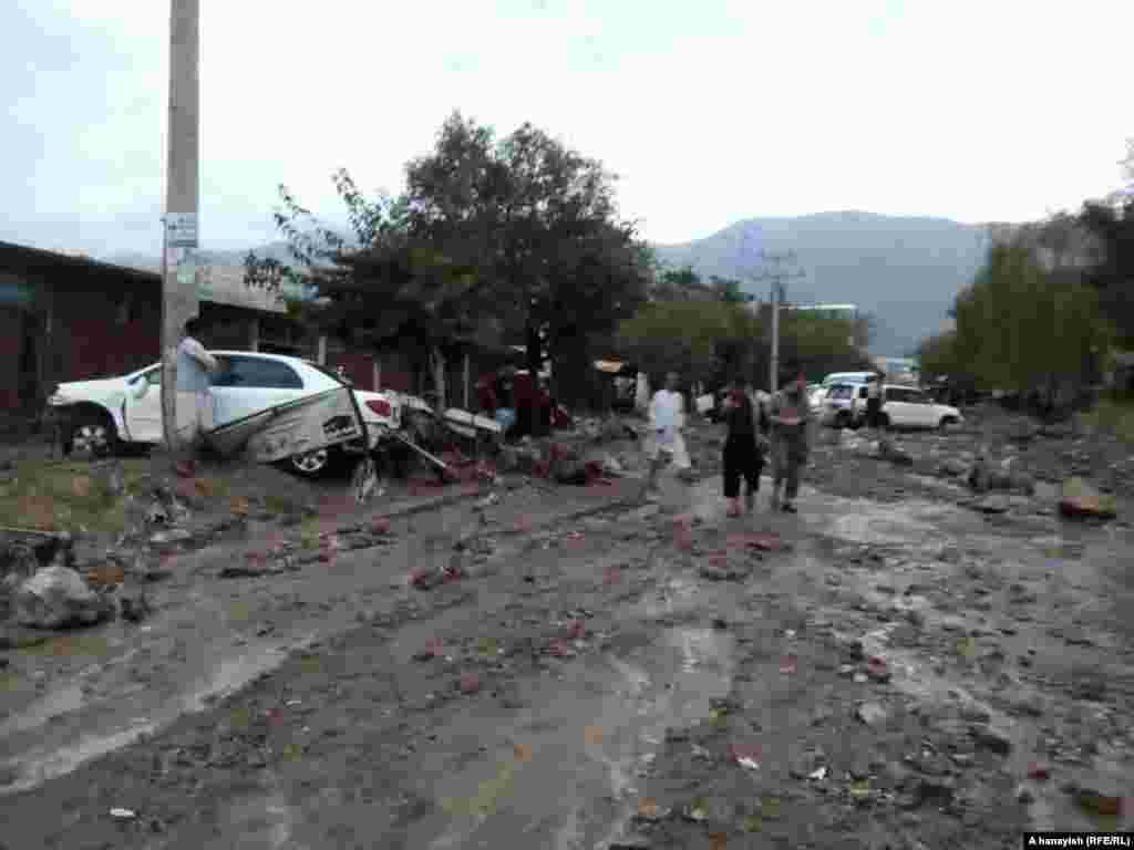 Vehicles are strewn across a mud-filled street in Charikar.