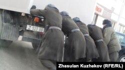 Сотрудники КУИС толкают машину с заключенными, которых везут в суд. Иллюстративное фото.