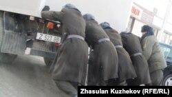 Түрме қызметкерлері тұтқындар мінген көлікті итеріп барады. Астана, 21 желтоқсан 2010 жыл. (Көрнекі сурет)