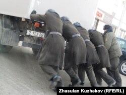 Сотрудники КУИС толкают машину с заключенными, которых везут в суд, Астана, 21 декабря 2010 года.