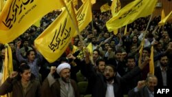 """Members the Islamic hard-line Basiji volunteer militia hold flags reading """"Down with the U.S.A."""" as they take part in a protest against America inside the former U.S. embassy in Tehran on November 2."""