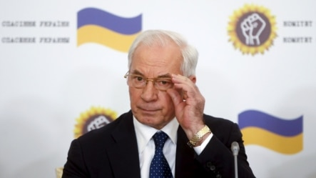 Ukraine's former Prime Minister Mykola Azarov adjusts his glasses as he attends a news conference in Moscow on August 3.