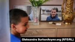 Син Сервера Мустафаєва Юнус біля фотографії батька в своєму будинку