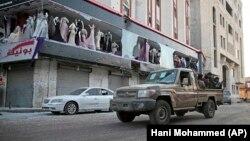 Повстанцы-хуситы проезжают недалеко от здания бывшей резиденции экс-президента Йемена Али Абдаллы Салеха. Сана, 4 декабря 2017 года.