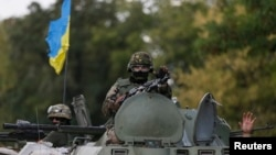 Ukrainian servicemen ride in an armored vehicle near Debaltseve, in the Donetsk region, on August 29.
