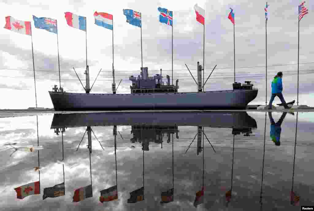 A man walks past flags and a model ship during the preparations for festivities commemorating the 75th anniversary of the arrival of the first Allied Arctic convoy in Russia during World War II. (Reuters/Maxim Zmeyev)