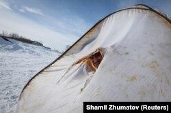 Ертіс өзеніне қатқан мұздың үстінде палатка ішінде отырған балықшы. Ақсу. 22 наурыз 2018 жыл.