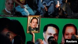 A supporter of former Pakistani prime minister Nawaz Sharif holds his picture
