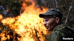 An armed pro-Russian separatist looks on as flames erupt from a gas pipeline after a shelling in Donetsk on August 15.