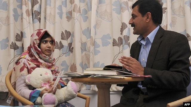 Malala Yousafzai (left) talks with her father Ziauddin at the Queen Elizabeth Hospital in Birmingham in November 2012.