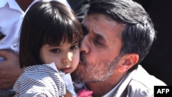 Ahmadinejad kisses a baby in Semnan.